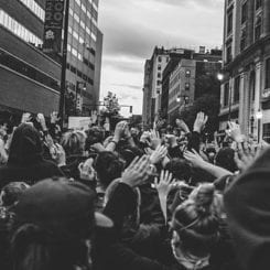 People out in the streets with their hands waving, like in a protest. Photographer unknown.