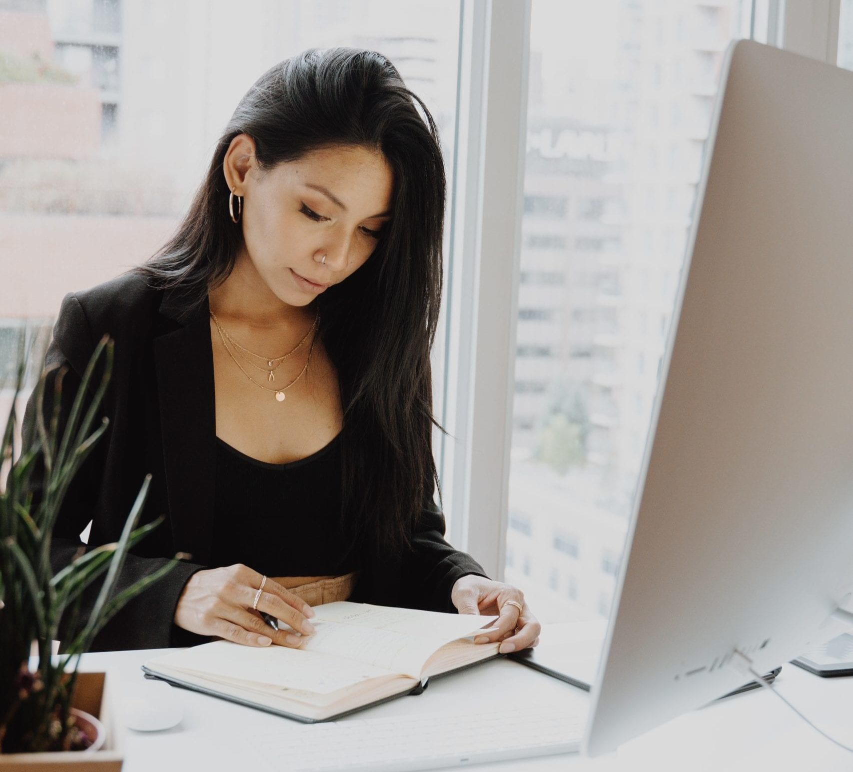 Photo: Woman at her desk writing in notebook by Keren Levand on Unsplash.